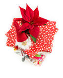 Poinsettia on stack of Christmas presents. Funny decorative dwarf and poinsettia on top of a stack of Christmas present boxes Stock Photography