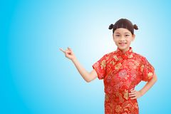 Point acting. Chinese Little girl finger point acting and wear cheongsam isolated on blue gradient background. Clipping path stock image
