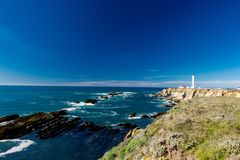 Point Arena Light House on a beautiful clear day with light clouds in the background. Dark blue sky royalty free stock photos