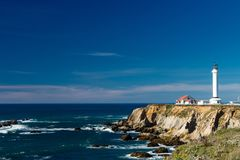 Point Arena Light House on a beautiful clear day with light clouds in the background. Dark blue sky with breakers on the rocks below stock photography