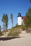 Point Betsie Lighthouse. Benzie County, Michigan.  Sandy beach in foreground, with trees and a partial view of the front of the lighthouse.  Clear blue skies Royalty Free Stock Images