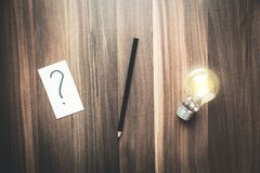 Point d'interrogation en papier avec le crayon et ampoule sur un bois de retour image libre de droits