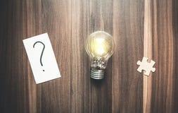 Point d'interrogation en papier avec le puzzle et ampoule sur un bois de retour photographie stock