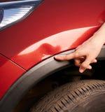 Point de doigt à l'éraflure de voiture photographie stock libre de droits