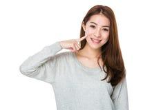 Point de doigt de femme à ses dents images stock