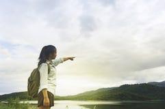 Point de main de femme de voyageur avec le sac à dos appréciant le coucher du soleil sur la crête Photo stock