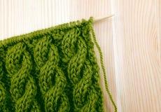 Point de tricotage vert de câble sur l'aiguille Images stock