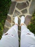 Point de vue avec des jeans et des chaussures de femme blanche Photographie stock