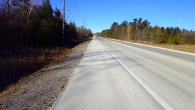 Point de vue de route rurale avec le trafic rare pendant la journée banque de vidéos