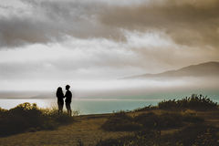 Point Dume Couple. Couple standing cliffside watching the sunset from Point Dume on a cloudy day, Malibu, California Stock Photography