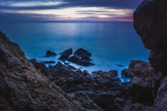Point Dume Rock Formations. Long-exposure photograph of silky smooth water flowing around rock formations after sunset at Point Dume State Beach with clouds in Stock Images