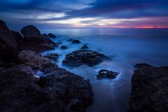 Point Dume Rock Formations. Long-exposure photograph of silky smooth water flowing around rock formations after sunset at Point Dume State Beach with clouds in Stock Photo