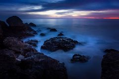 Point Dume Rock Formations. Long-exposure photograph of silky smooth water flowing around rock formations after sunset at Point Dume State Beach with clouds in Royalty Free Stock Image