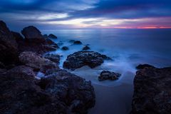 Point Dume Rock Formations. Long-exposure photograph of silky smooth water flowing around rock formations after sunset at Point Dume State Beach with clouds in Royalty Free Stock Photos