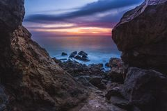 Point Dume Rugged Trail. Long-exposure photograph of silky smooth water flowing around rock formations after a colorful sunset with clouds in the sky, viewed Stock Image