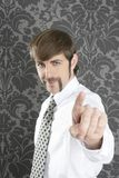 Point finger retro businessman salesperson. On gray vintage wallpaper royalty free stock image