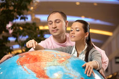 Point on globe. The girl shows to the guy a place on the big copy of globe royalty free stock photography