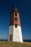 Point Judith Lighthouse. Rhode Island, USA. Daytime image of white and red brick and stone lighthouse with the sea in the background Royalty Free Stock Photography