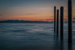 Point Roberts pilings and silky water at night time Stock Photos