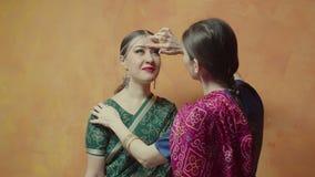 Point rouge de collage femelle de bindi de plan rapproché à l'ami banque de vidéos