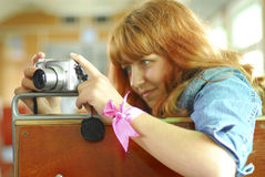 Point-and-shoot camera. Beautiful red girl aiming with p/s camera. Shallow dof used with focus on the camera stock images