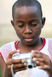 Point and shoot portrait of a boy. Boy looking at a recently taken photo on the back of his camera Stock Image