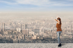 Point somewhere. Asian young woman point somewhere over the city, full length portrait royalty free stock image