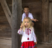 Children in national ukrainian costumes. Old house. Little girl tries to show me the crow stock photos