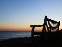 Point of View. A bench with a view out to sea as the sun sets Royalty Free Stock Photos