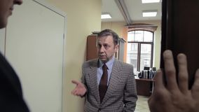 Point of view business adult boss chastises worker man in office cabinet. Point of view business adult caucasian boss in grey checker jacket chastises worker man stock footage