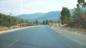 Point of view of car driving at road in scenic mountain environment. Auto riding through highway at summer day