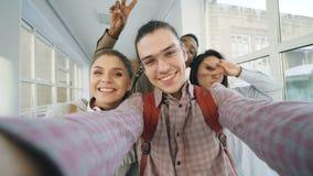 Point of View de cuatro amigos multi-étnicos atractivos alegres positivos que hablan las fotos del selfie que sostienen smartphon metrajes
