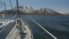Point of View de navegar el yate en el mar y las montañas con los picos nevosos almacen de video