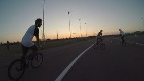 Point of View del ciclista que se divierte con sus amigos del motorista que realizan diversos tirones y trucos del salto afuera e almacen de video