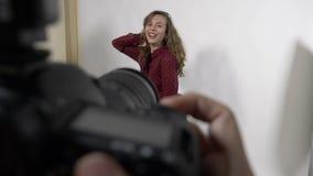 Point of View del fotógrafo que hace el tiroteo de foto famoso de la campaña de la marca de la ropa en estudio con un modelo feme metrajes