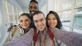 Point of View del grupo multi-étnico positivo de amigos que hablan las fotos del selfie que sostienen smartphone y que se diviert almacen de video
