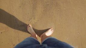Point of View del hombre joven que camina en la arena de oro en la playa del mar Piernas masculinas que caminan cerca del océano  metrajes