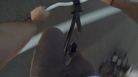 Point of View del montar a caballo atlético y de hacer del ciclista el salto del conejito engaña en su bici - almacen de video