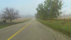 Point of view drive down a country road through fog stock video footage
