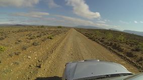 Footage out of a window of a 4x4. Point of view footage taken out of the window of a 4x4 as it travels at speed along a dusty graded gravel dirt road stock video footage