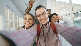 Point of view of four positive cheerful attractive multi-ethnic friends talking selfie photos holding smartphone and stock footage
