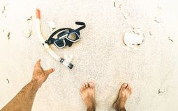 Point of view of hand picking up snorkeling mask at the beach stock photo