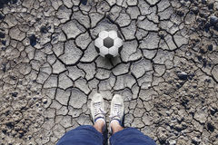Point of view man with soccer ball standing on cracked soil. Man with white shoes standing on cracked dried soil ground with a soccer ball. Conceptual soccer royalty free stock image