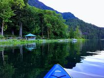 A point of view perspective from a person kayaking on the ocean on a beautiful peaceful evening along the shores of forested shore. Line.  This is outside of stock images
