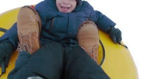 Point of View que el niño pequeño feliz sledding en montaña a través de la nieve vuela en un trampolín en la cámara lenta almacen de metraje de vídeo