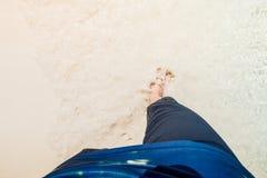 Point of View que mira abajo de la gente que camina en la playa con desnudo Foto de archivo