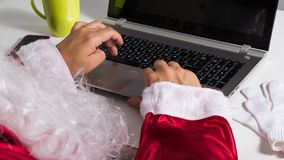 Point of view of Santa Claus showing hands typing at laptop keyboard. Point of view of Santa Claus or Father Christmas showing hands typing at laptop keyboard stock photos