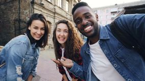Point of view shot of attractive young men and women travelers taking selfie in the street posing and laughing holding