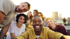 Point of view shot of young people multiethnic group taking selfie and holding camera, men and women are looking at