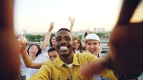 Point of view shot of handsome African American man partying with friends on rooftop, dancing and having fun with drinks